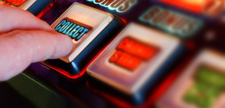 Finger pressing a button on a slot machine