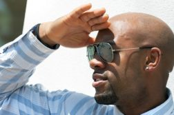 Man with sunglasses shielding his eyes