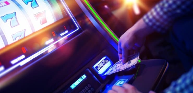 Man putting money into a slot machine