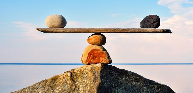 Two rocks balancing on a wooden plank