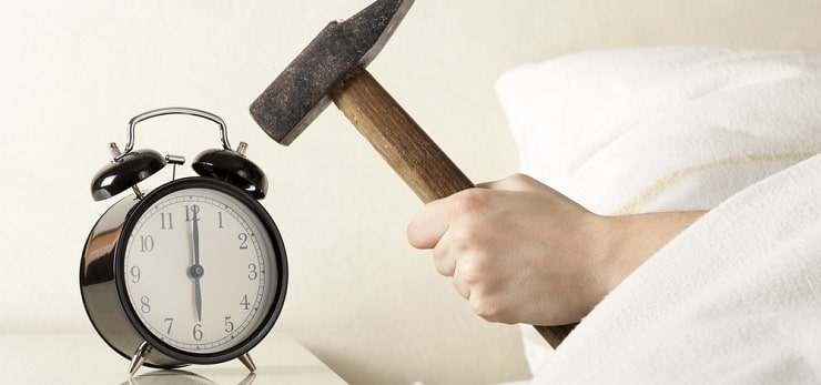 Man in bed hitting alarm clock with a hammer